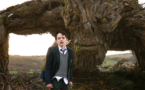 A MONSTER CALLS (2016) Conor (Lewis MacDougall) and The Monster (performed and voiced by Liam Neeson)
